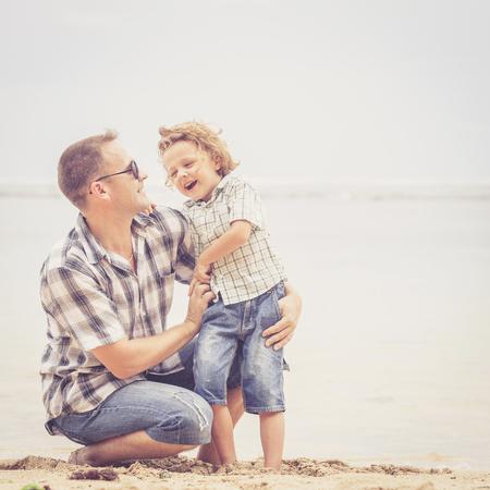 父と息子のビーチでの一日の時間でプレーします。フレンドリーな家族の概念。