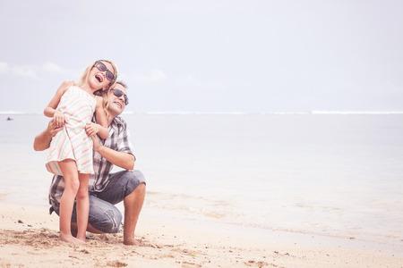 Padre e hija jugando en la playa en el día. Concepto de la familia.
