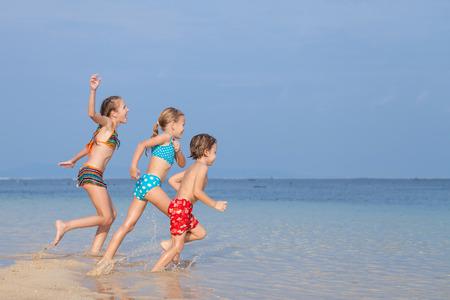Drie gelukkige kinderen spelen op het strand van de dag tijd