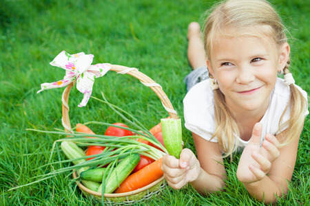 little girl eating: Happy little girl lying on the grass with a basket of vegetables at the day time. Concept of healthy food.