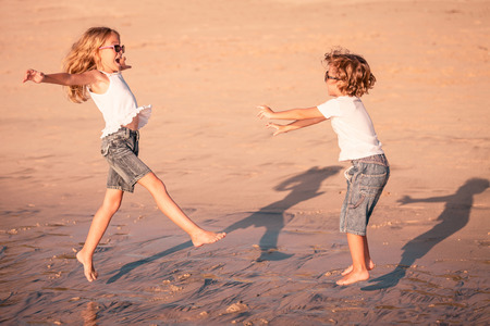 Two happy children  playing on the beach at the day time photo