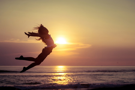 mujeres y niños: Niña feliz saltando en la playa en la puesta del sol