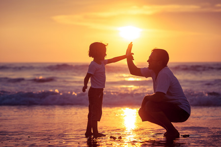 Vader en zoon spelen op het strand bij de zonsondergang tijd. Concept van de vriendelijke familie.