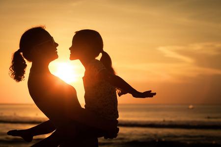 Madre e hija jugando en la playa de la puesta del sol. Concepto de la familia. Foto de archivo