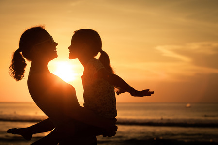 daughter mother: Mother and daughter playing on the beach at the sunset time. Concept of friendly family.