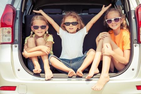 familia viaje: Feliz hermano y sus dos hermanas se están sentando en el coche en el tiempo del día Foto de archivo