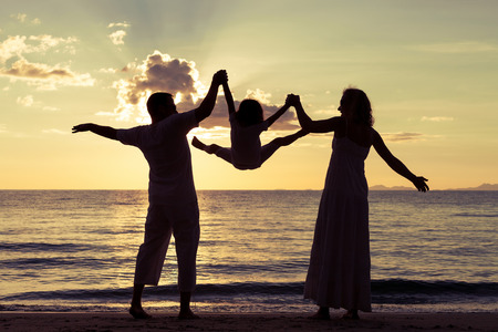 family time: Silhouette of happy family who playing on the beach at the sunset time. Concept of friendly family. Stock Photo