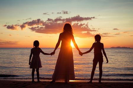 mom daughter: Madre e hijas de pie en la playa de la puesta del sol. Concepto de la familia.