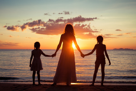 Mother and daughters standing on the beach at the sunset time. Concept of friendly family.