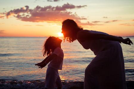Moeder en zoon spelen op het strand bij de zonsondergang tijd. Concept van vriendelijke familie.