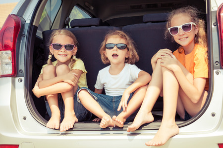 가족: 행복 형제와 그의 두 자매는 낮 시간에 차에 앉아있다