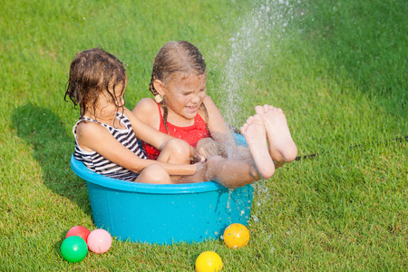 hosepipe: brother and sister playing with water near a house at the day time Stock Photo