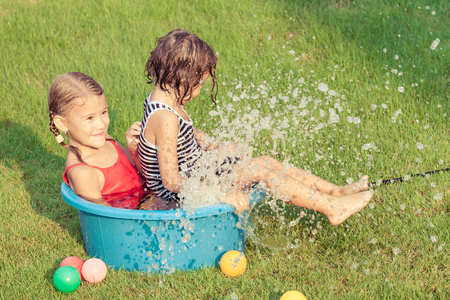 moisten: brother and sister playing with water near a house at the day time Stock Photo