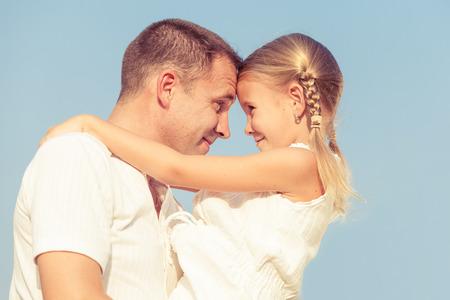 Papá e hija jugando cerca de una casa en el momento en día. Concepto de la familia.