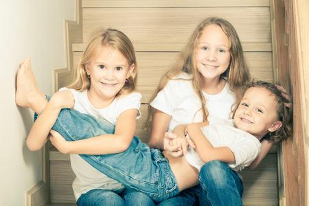Portret van gelukkige kinderen die zittend op de trap in het huis. Het concept van een broer en zus voor altijd. Stockfoto