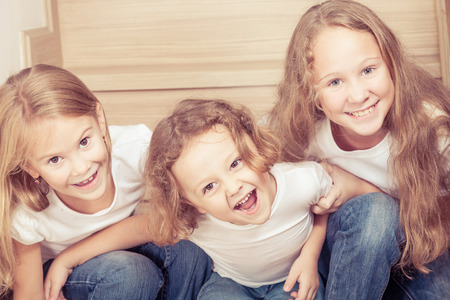 young girl smiling: Portrait of happy children which are sitting on the stairs in the house. The concept of a brother and sister forever.
