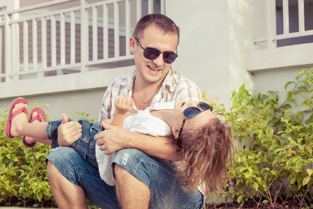 Dad and son playing near a house at the day time. Concept of friendly family. photo
