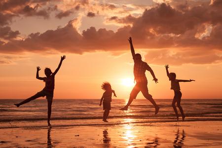 personas saltando: Padre y niños que juegan en la playa de la puesta del sol. Concepto de la familia.
