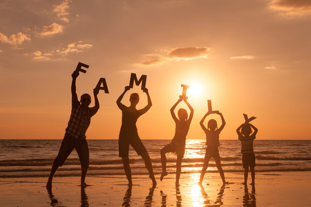 Happy family standing on the beach at the sunset time. They keep the letters forming the word 版權商用圖片