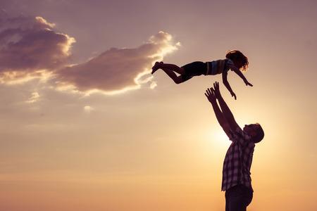 Padre e hijo jugando en la playa en el tiempo del día. Concepto de la familia.