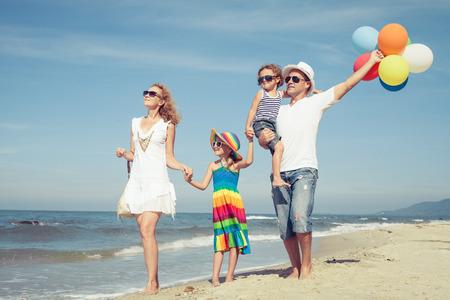 Glückliche Familie spielen mit Luftballons am Strand von der Tageszeit. Konzept der freundlichen Familie.