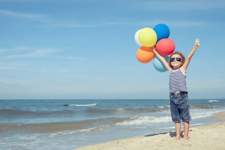 young boy: Portrait of little boy with balloons standing on the beach at the day time