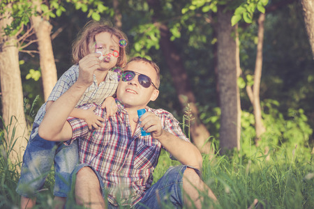 holiday home: Father and son playing at the park at the day time. Concept of friendly family. Stock Photo