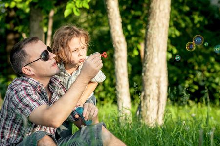 viaje familia: Padre e hijo que juegan en el parque en el día. Concepto de la familia.