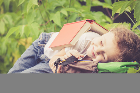 kids having fun: little boy with book lying in the park at the day time Stock Photo