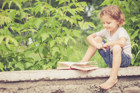 cool kids: little boy with book sitting in the park at the day time Stock Photo