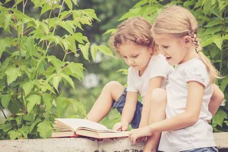 little boy and girl with book sitting in the park at the day time