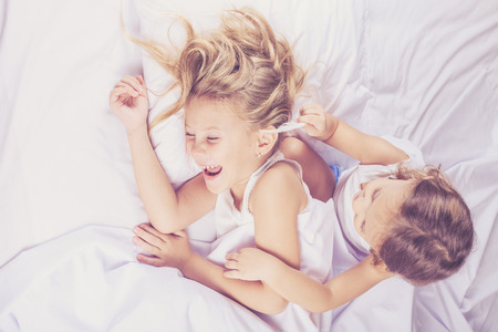 Adorável irmão e irmã deitada na cama em casa. Conceito de irmão e irmã Together Forever Imagens