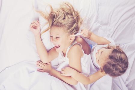 cama: Hermano precioso y hermana acostado en la cama en su casa. Concepto de hermano y hermana Juntos para siempre
