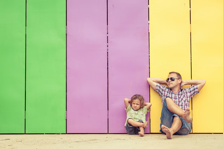 Father and son playing near the house at the day time. They sitting near are the colorful wall. Concept of friendly family.