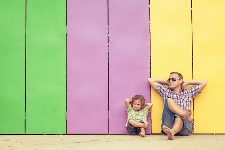 Vader en zoon spelen tegenwoordig bij het huis. Zij zitten dichtbij zijn de kleurrijke muur. Concept van vriendelijke familie.