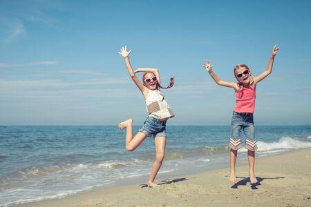 kinder spielen: Glückliche Kinder spielen am Strand an der Tageszeit