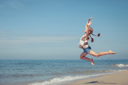 school sports: Teen  girl  jumping on the beach at the day time