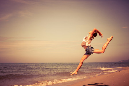 lifestyle: Muchacha adolescente que salta en la playa en el momento día
