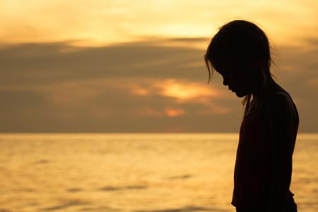 Portrait of sad blond little girl standing on the beach at sunset time. Standard-Bild