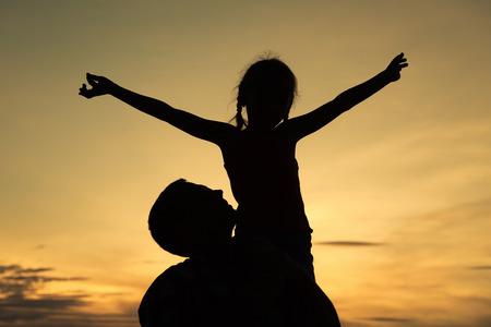 padre e hija: Padre e hija jugando en la playa en la puesta del sol. Concepto de la familia.