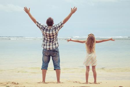 lifestyle: Padre e hija jugando en la playa en el día. Concepto de la familia.
