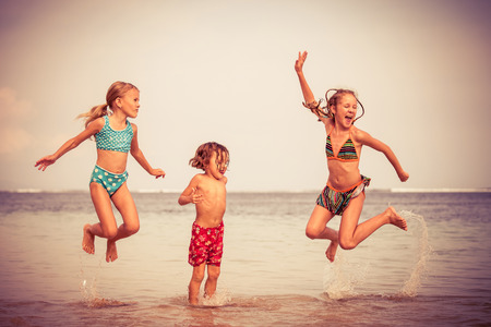 vacation: Three happy children  playing on the beach at the day time
