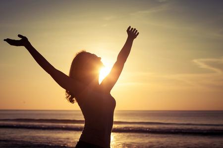 vrouw open armen onder de zonsondergang op zee