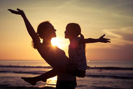 Moeder en dochter spelen op het strand bij de zonsondergang tijd. Concept van de vriendelijke familie.