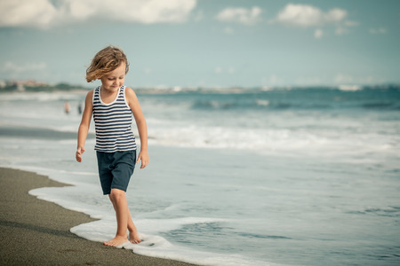 cool boy: Portrait of little boy jumping on the beach at the day time
