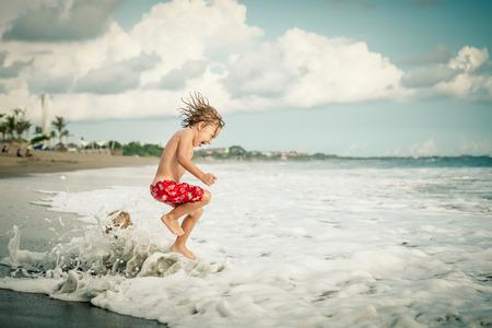 Portret van weinig jongen springen op het strand van de dag de tijd Stockfoto