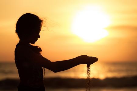 일몰 시간에 해변에 서있는 슬픈 십 대 소녀의 초상화입니다.