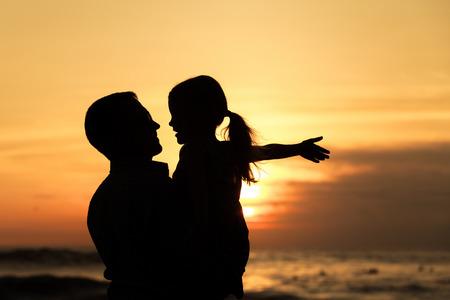 父と娘の日没時にビーチで演奏します。フレンドリーな家族の概念。