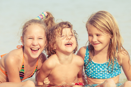kids outside: Three happy children  playing on the beach at the day time