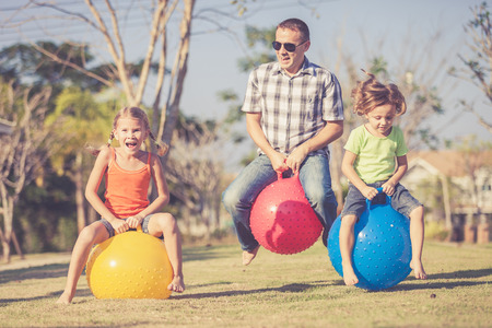 fun: Dad and children playing on the lawn in front of house at the day time Stock Photo